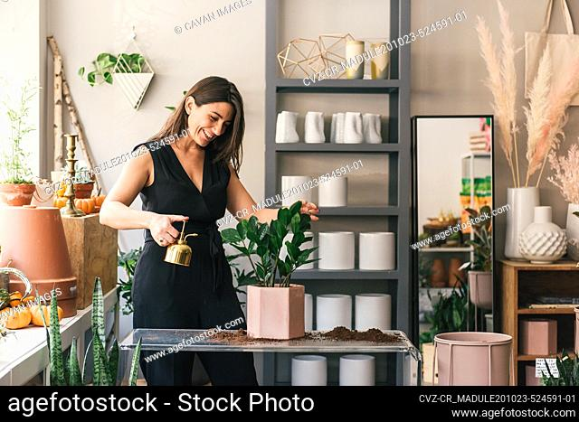 Smiling business owner waters plants in her flower shop