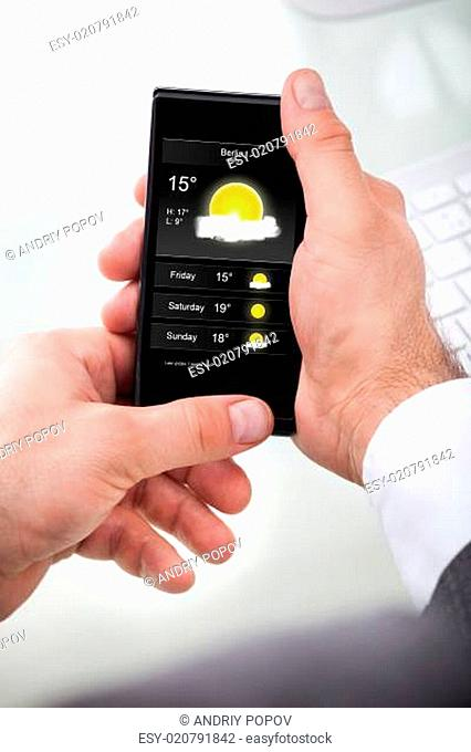 Businessman Looking Weather Forecast On Cellphone
