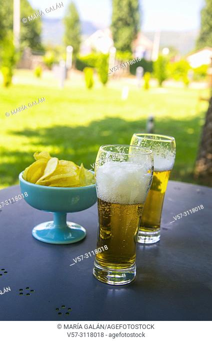 Two glasses of beer with chips in a terrace. Spain