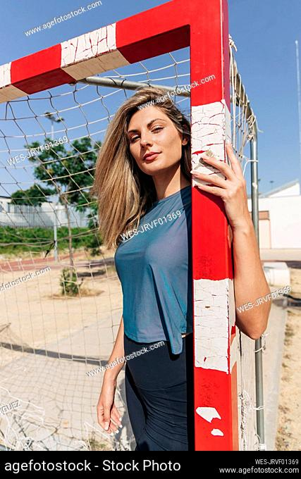 Confident blond woman at goal post on sunny day