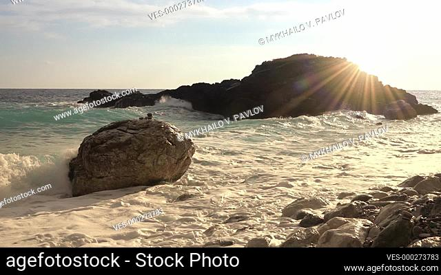 Sunny morning on the rocky shore. A wave is breaking against a rock with many splashes. Slow motion