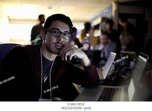 Portrait focused male hacker working hackathon at laptop in dark office