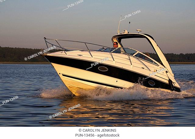 Cruising around Poole Harbour in a speed boat in the evening light in summer, England