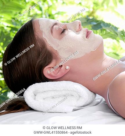 Woman with facial mask lying on a massage table