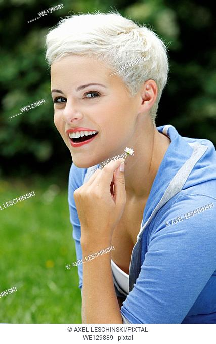 Young woman sitting in grass enjoying sun