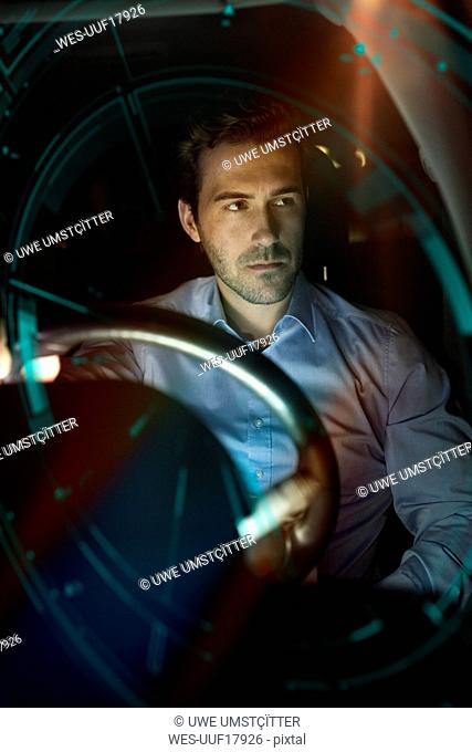 Businessman in car at night surrounded by virtual tachometer