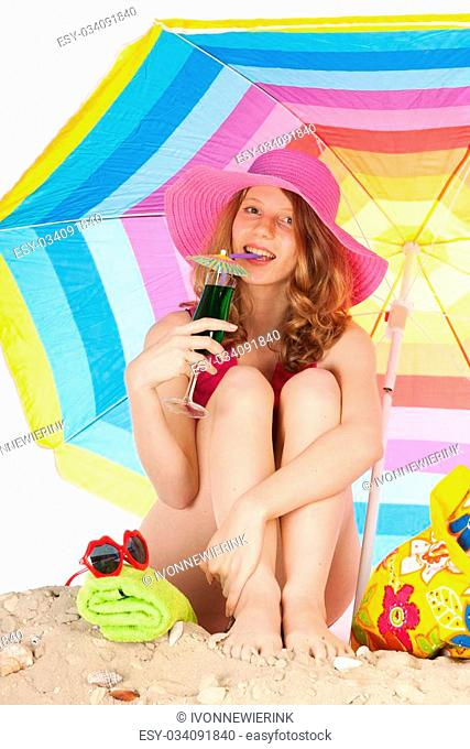 woman sitting at the beach with pink hat under colorful parasol isolated over white background