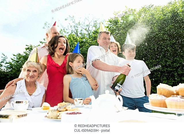 Family celebrating birthday, man opening champagne
