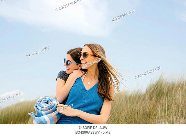 Two young female friends carrying picnic blanket on dunes