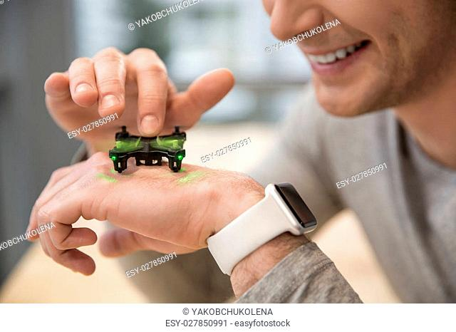 Close up of arm of young man watching at the small quadrocopter in move. He is touching the moving propeller and smiling