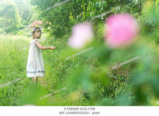 Girl wearing flower wreath on meadow