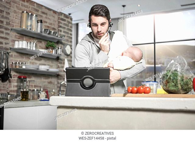 Father with headset and tablet in kitchen holding baby