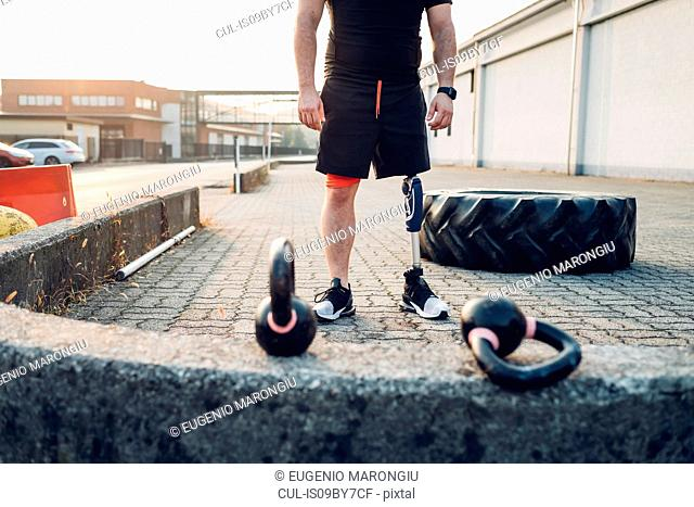 Man with prosthetic leg beside training tyre and kettlebells