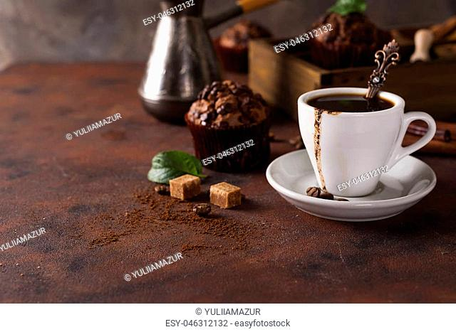Cup of coffee with cooffee beans and mint leaves, wooden box with grains of coffee and spices, capcake on a stone background