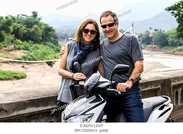 A couple stand posing by a motorcycle with a mountainous landscape in the distance; Luang Prabang, Luang Prabang Province, Laos