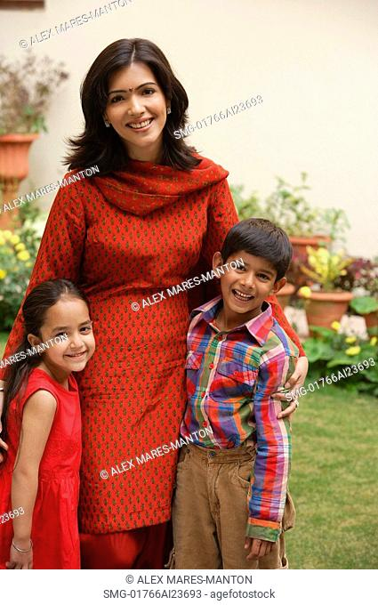 mother standing with son and daughter in garden, smiling at camera