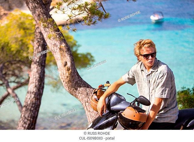 Young man sitting on moped at coast, Majorca, Spain