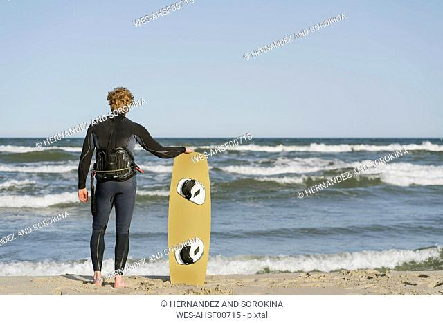 Rear view of kiteboarder standing with his surf board at the beach