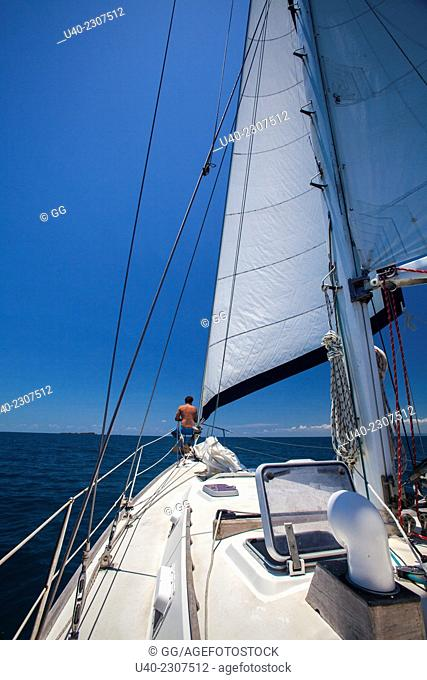 Belize, man sitting on bow of sailboat
