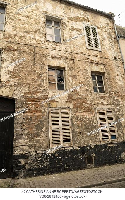 Abandoned building in historic quarter with broken glass, eroded plaster work and shutters, Cambrai, France
