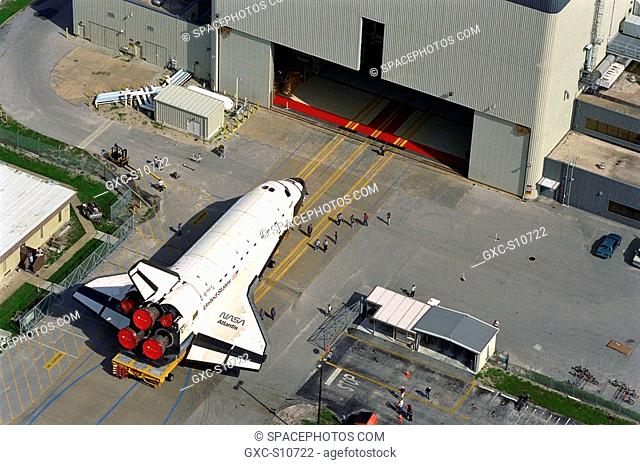 08/11/1997 --- Carried atop an orbiter transporter, the Space Shuttle orbiter Atlantis rolls out of Orbiter Processing Facility Bay 3, in background