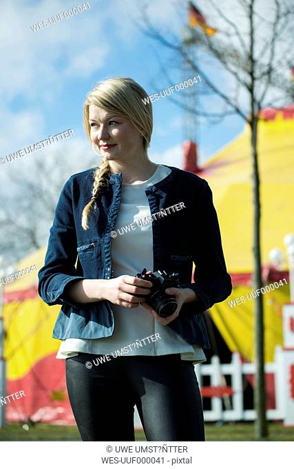 Germany, Mannheim, Young woman with camera in front of circus tent