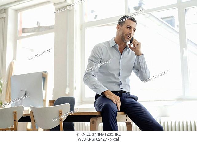 Businessman in office talking on cell phone