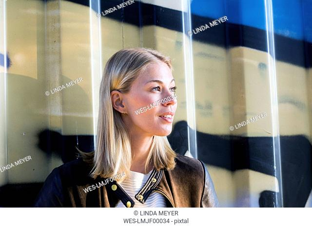 Portrait of blond woman in front of container looking at distance