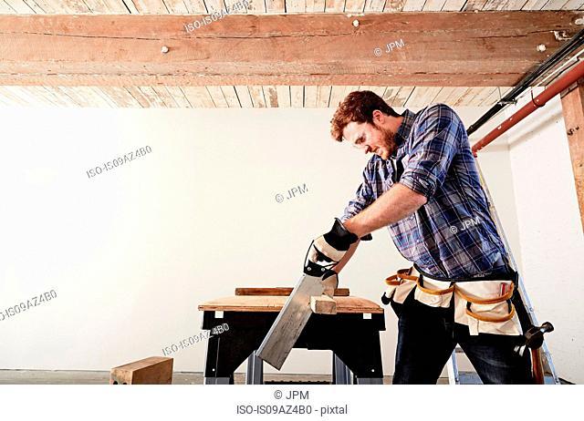 Carpenter in workshop sawing timber