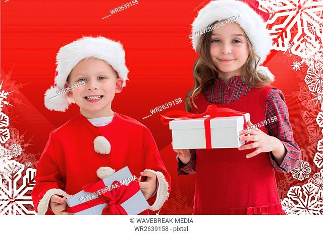 Two happy kids in santa costume holding a christmas gift