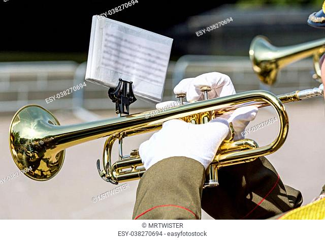 military musician playing on gold trumpet in army orchestra