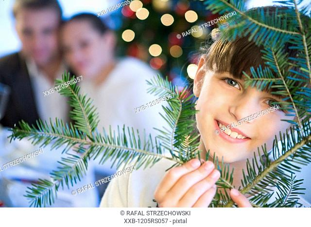 daughter with parents near christmas tree