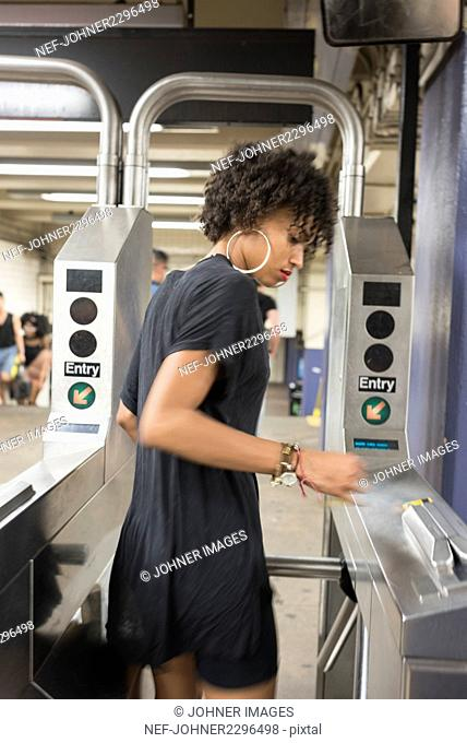 Young woman going through turnstile at subway station