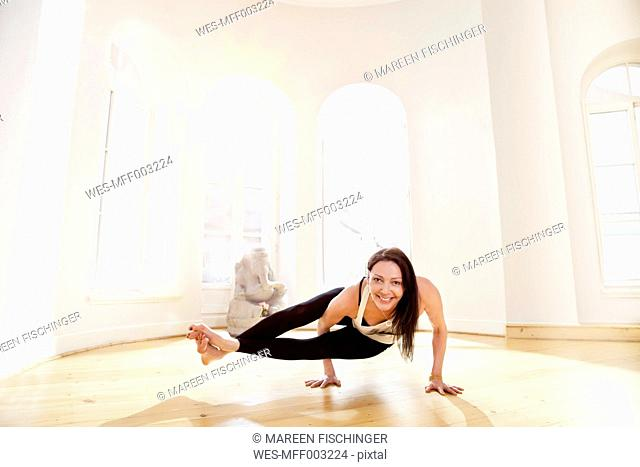 Woman in sunny yoga studio holding Astavakrasana pose