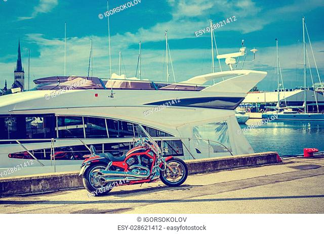 Beautiful motorcycle on the pier on the background of yachts. Cross process