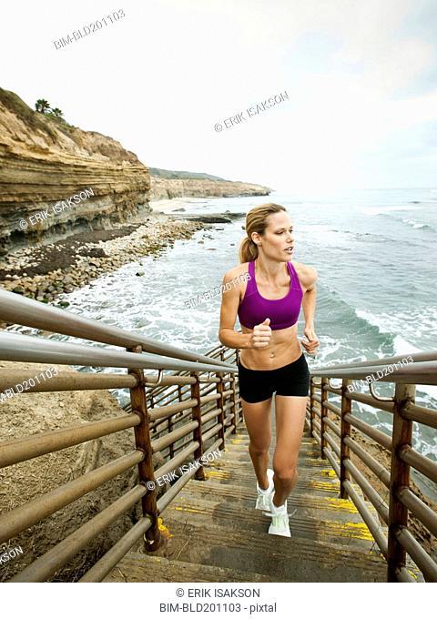 Caucasian woman running up stairs next to ocean