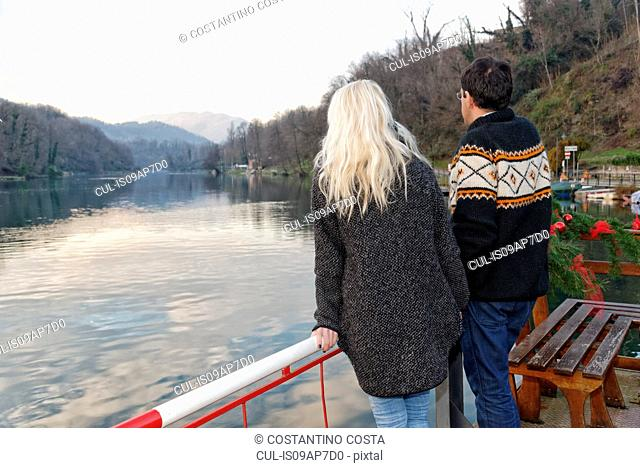 Heterosexual couple standing beside lake, Lombardy, Italy, rear view