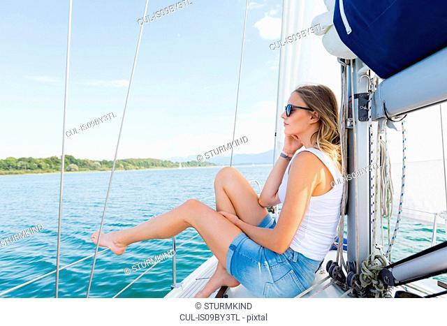Young woman sailing on Chiemsee lake, Bavaria, Germany