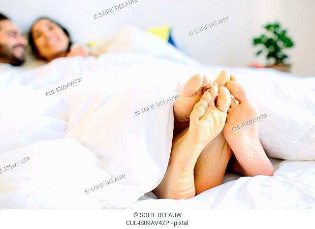 Happy young couples bare feet sticking out from duvet