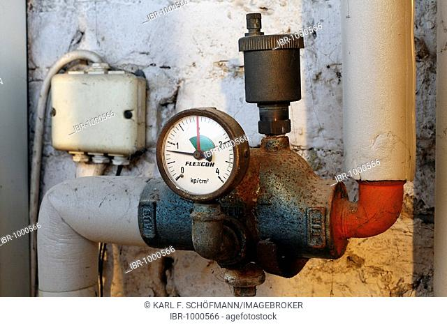 Old manometer on heating pipes in a house cellar, natural gas heating system prior to modernisation, Germany, Europe