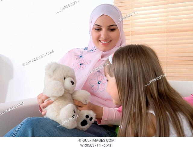 Mother and daughter sitting on sofa, playing with teddy bear