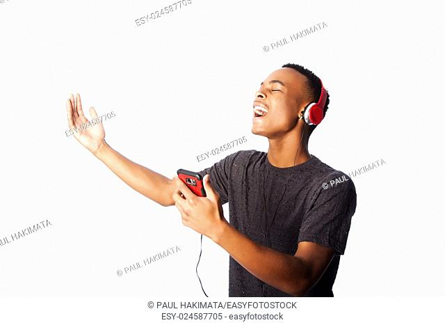 Handsome African teenager happily singing along while listening to music, on white