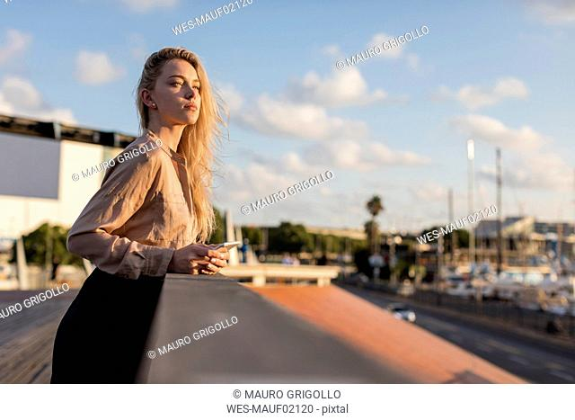 Beautiful young businesswoman with cell phone at the waterfront