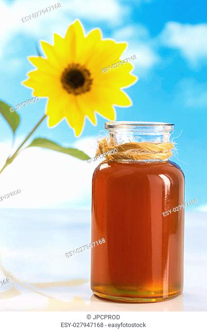 A jar of honey with sunflowers on white board