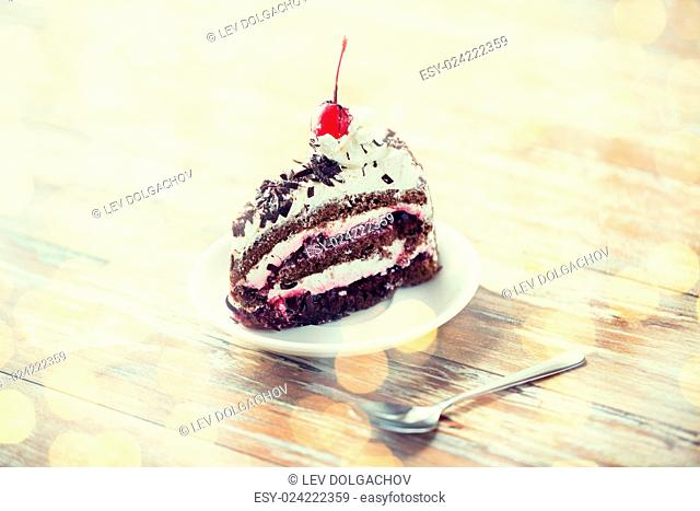 food, junk-food, culinary, baking and holidays concept - piece of delicious cherry chocolate layer cake on saucer with spoon on wooden table over holidays...