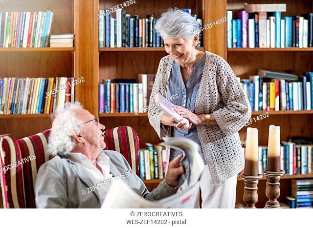 Senior man and woman sitting in library, reading book and newspaper