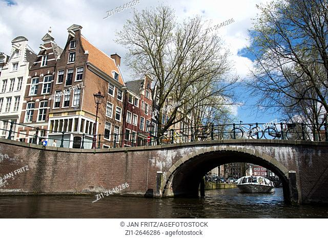 bridge, canal and old historic buildings in amsterdam holland