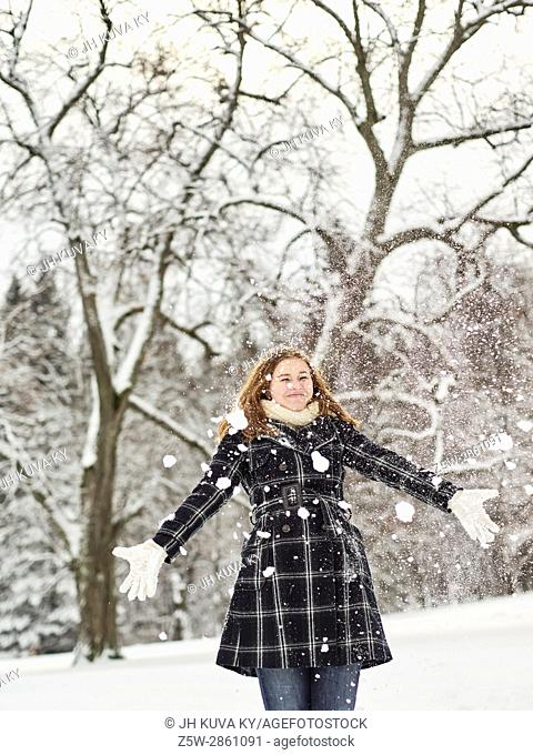 Beautiful young girl wearing a winter coat and throwing snow up in the air, Finnish winter day on February