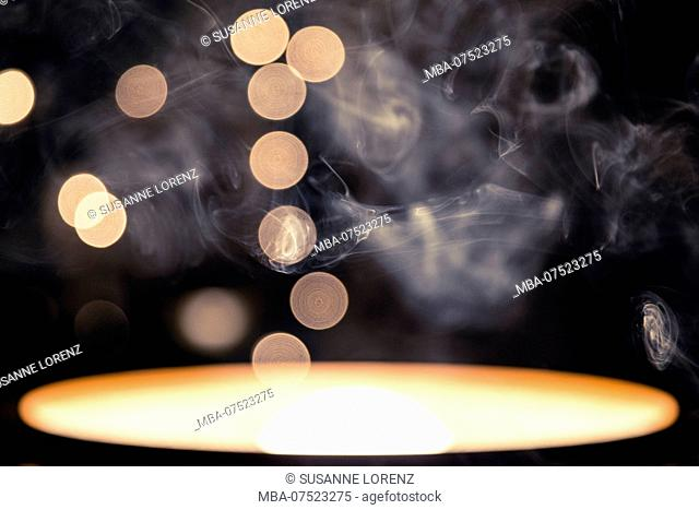 Abstract photo of a pendant lamp turned by 180 degrees, cigarette smoke in the foreground, Bokeh, string of lights, dark background