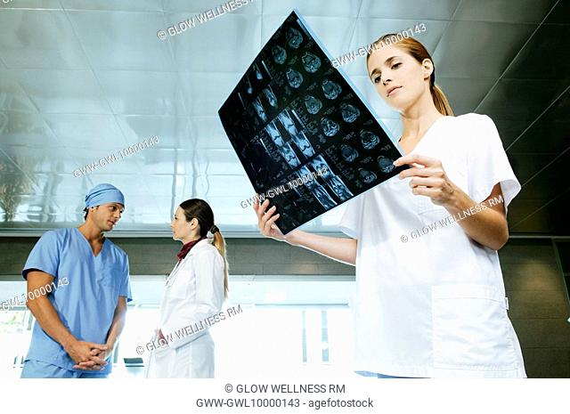 Female nurse examining an X-Ray with her colleagues discussing in the background